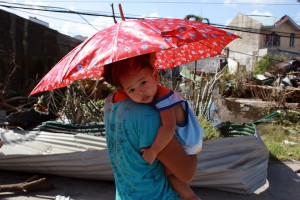 A mother carries her daughter as they walk in Tacloban, Leyte